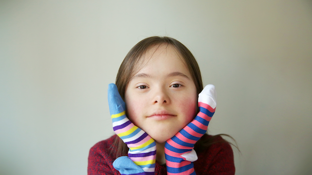 A young person with two different socks on her hands